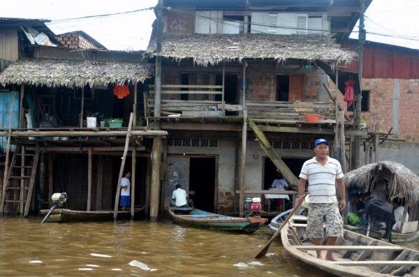 A man stands in a canoe in Iquitos, Peru